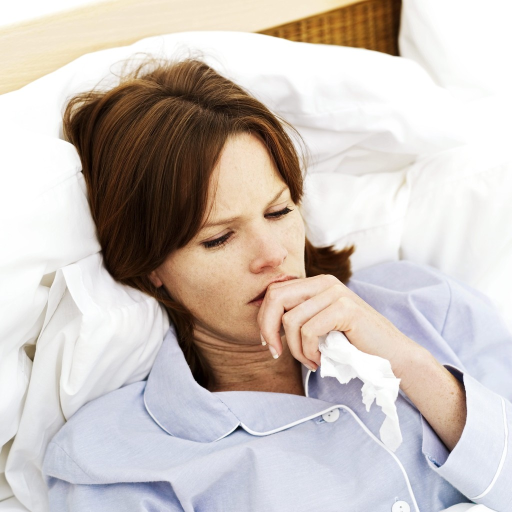 Sick Young Woman Lying in Bed